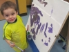Kayden painting at the easel